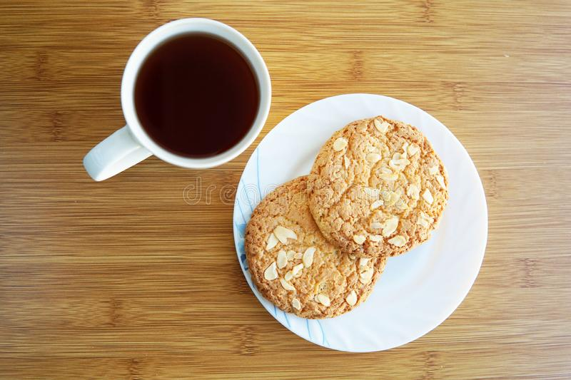 A cup of tea and two cookies. Cup of tea and saucer with cookies with nuts on the table. Top view breakfast drink food white dessert background plate snack sweet royalty free stock image