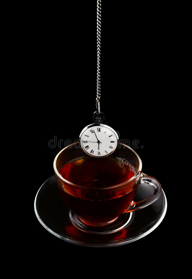 Cup of tea and watch isolated. On black background stock photography