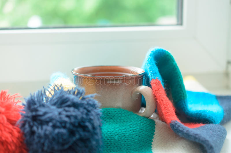 A cup of tea on a window sill wrapped in a scarf. Warming up the house. royalty free stock images