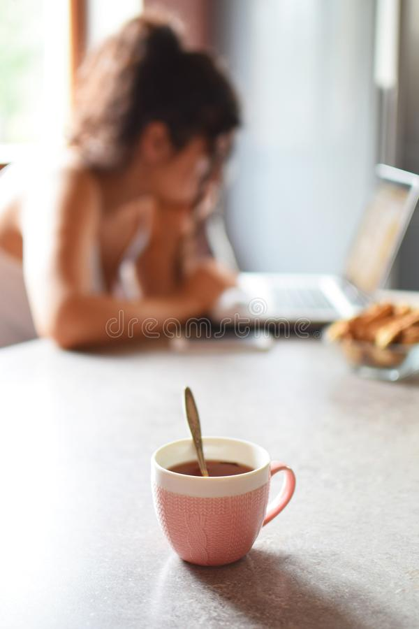 Cup of tea and woman working royalty free stock images