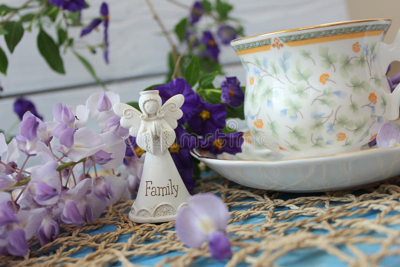 A cup of tea on a wooden blue table with a bouquet of colored field flowers and white small angel of family stock image