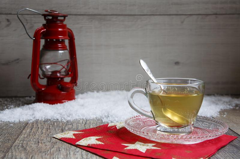 Cup of tea on wooden table with red latern stock photo