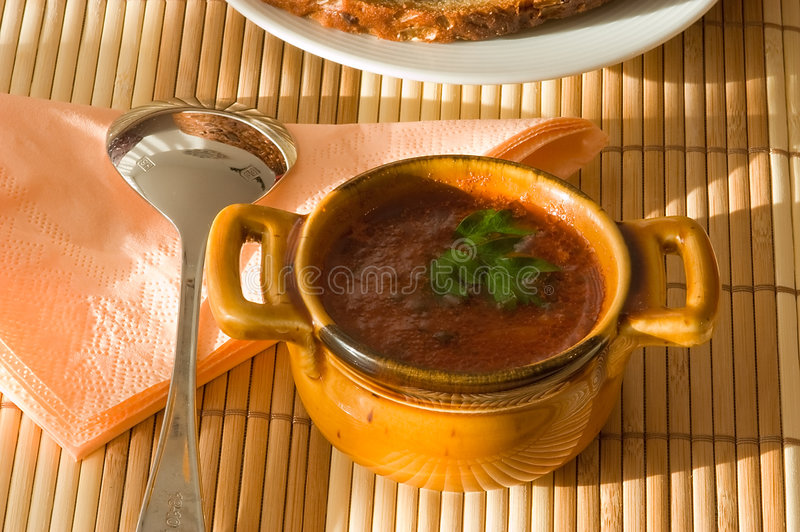 Cup of tomato soup on bamboo serviette. Cup of tomato soup with the spoon, a napkin and a number laying bread on a plate. On bamboo serviette royalty free stock image