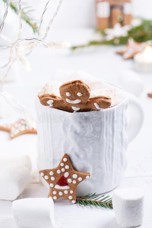 Cup of traditional hot chocolate with marshmallows and gingerbread on white table.  Christmas drink in New Year decorations.  royalty free stock photography