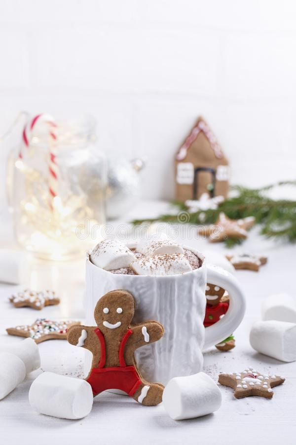 Cup of traditional hot chocolate with marshmallows and gingerbread on white table.  Christmas drink in New Year decorations. Copy space stock image