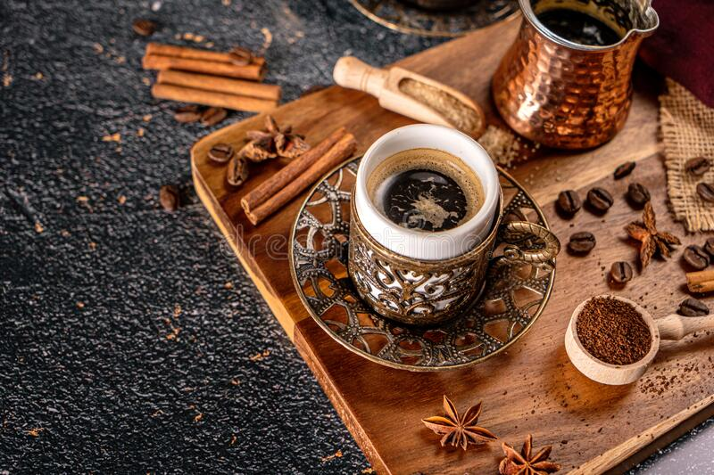 Cup of turkish coffee on black background with spices, coffee beans and sand coffee pot royalty free stock photo