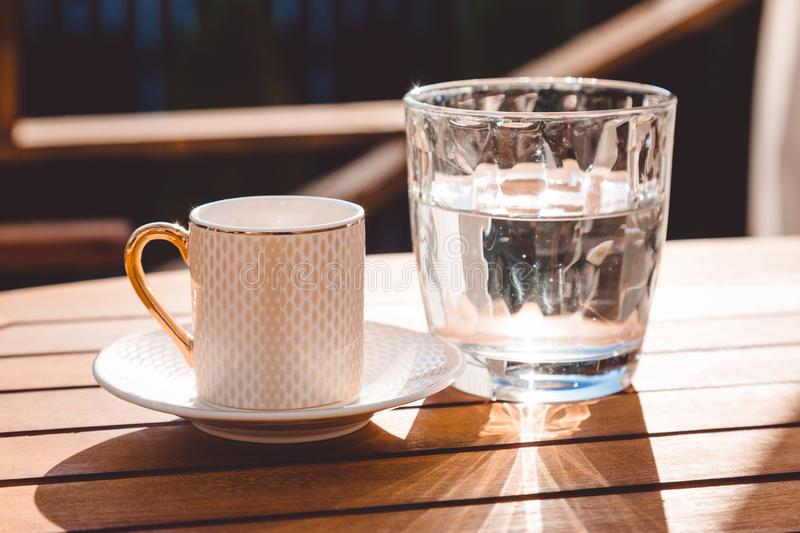 A cup of Turkish coffee and a glass of water on the wooden table on a terrace in a garden, coffee break. Workplace, sunny day, chilling time, restaurant, cafe royalty free stock image