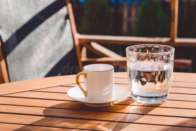 A cup of Turkish coffee and a glass of water on the wooden table on a terrace in a garden, coffee break. Workplace, sunny day, chilling time, restaurant, cafe stock image