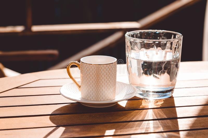 A cup of Turkish coffee and a glass of water on the wooden table on a terrace in a garden, coffee break. Workplace, sunny day, chilling time, restaurant, cafe stock photography