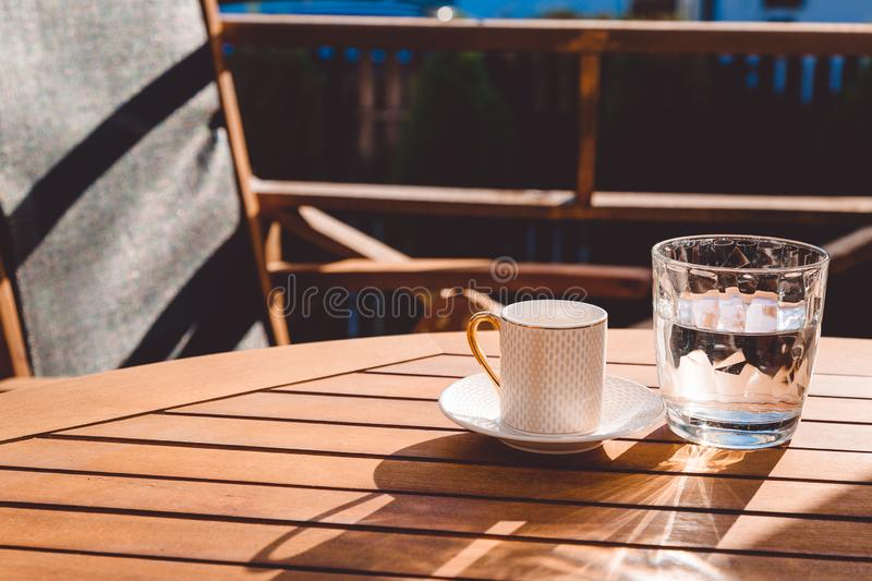 A cup of Turkish coffee and a glass of water on the wooden table on a terrace in a garden, coffee break. Workplace, sunny day, chilling time, restaurant, cafe stock photo