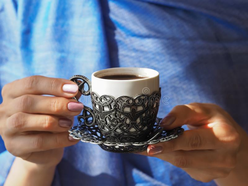 A cup of Turkish coffee holding women hands. royalty free stock images