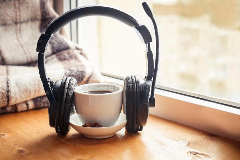 Cup with warm drink with headphones on wooden table in front of window. Autumn. Concept royalty free stock photos