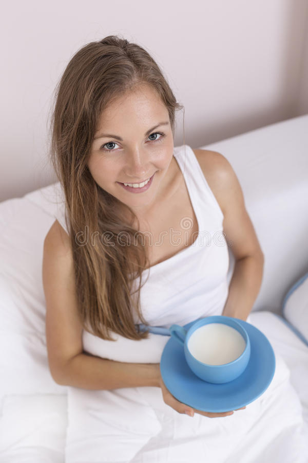 Cup of warm milk before sleep. Beautiful, young woman sitting in bed in the evening, holding a large blue cup filled with warm milk, drink for a good nights royalty free stock photo