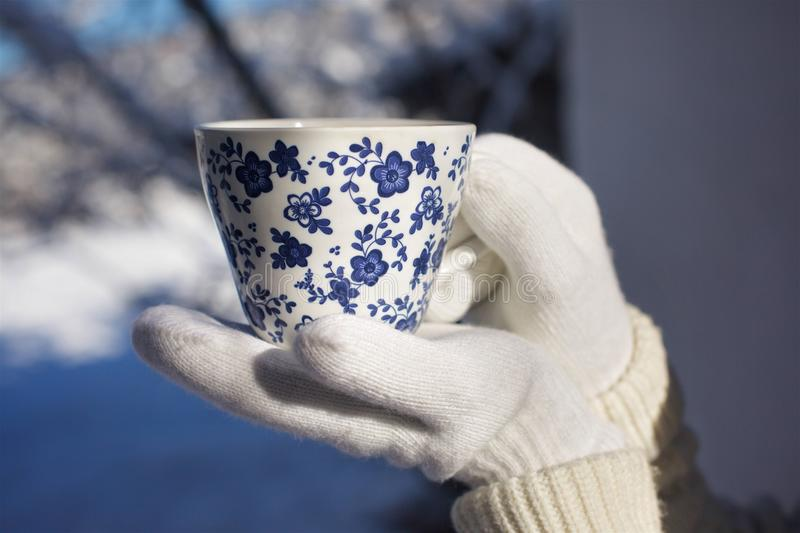 A Cup of warm tea. Man`s hands holding a Cup of warm tea. Hands in knitted gloves royalty free stock photo