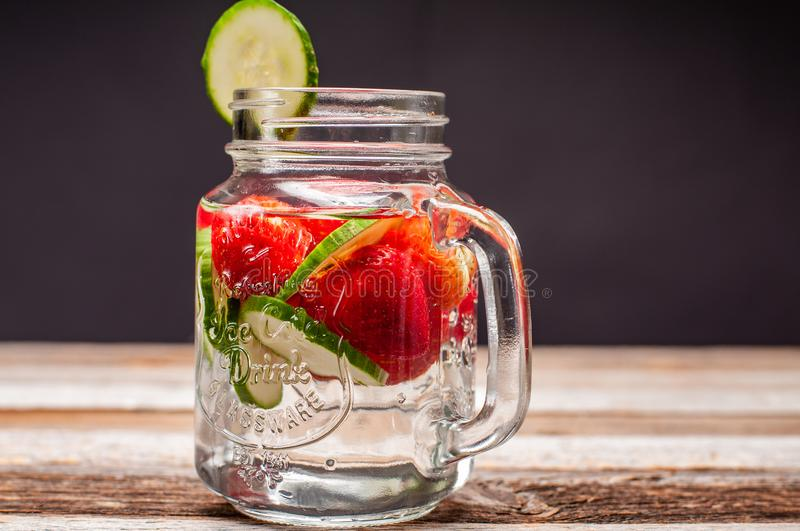 Cup of water with fruit, cucumber, strawberry stock photography