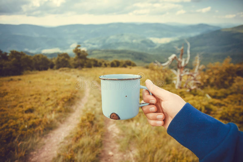 Cup of water or hot tea in tired hand of a lonely tourist. Hike concept in green grass mountains at cloudy weather. stock images