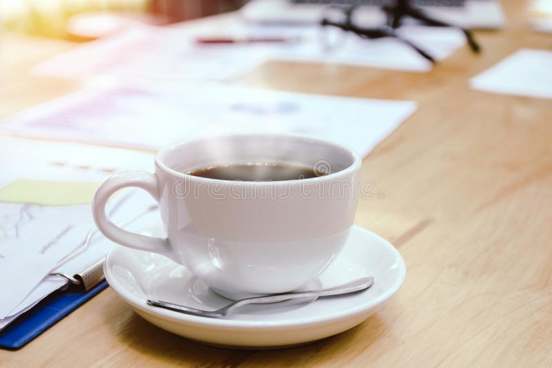 Cup of white coffee with smoke. folders and documents on desk with glasses and laptop on wood. Table royalty free stock images