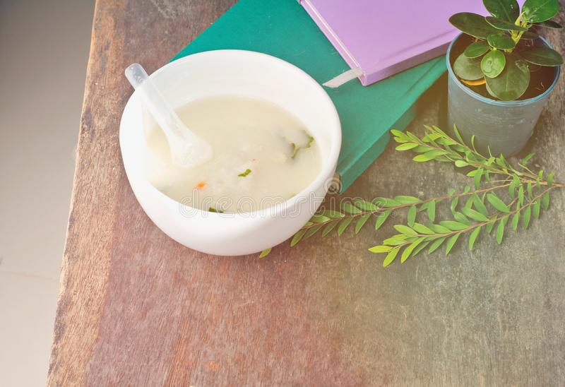 Cup of white porridge, breakfast, put on an old wooden table Green note book Tree decorated on a table,. Light pine branches stock photos