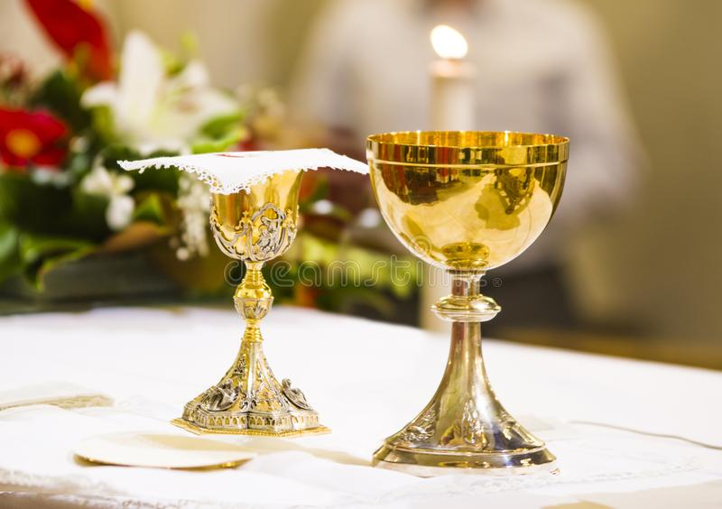 Cup with wine and ciborium with host on the altar of the holy mass stock images