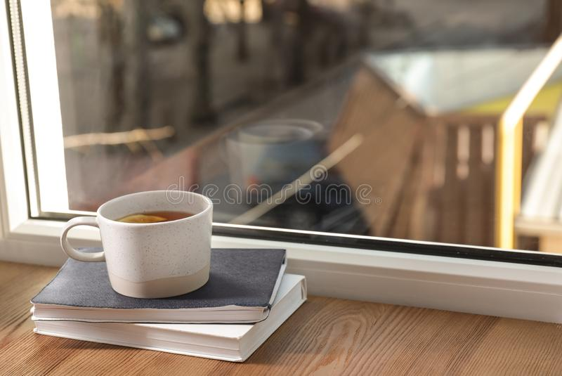 Cup of winter drink and books on windowsill. Space for text stock image