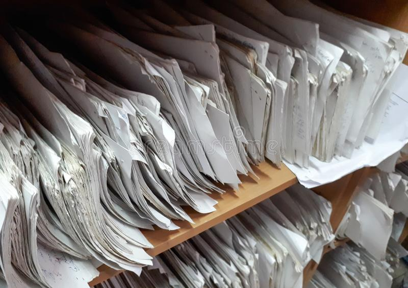 A cupboard full of paper files. / inefficiency of paper based filing system royalty free stock photo