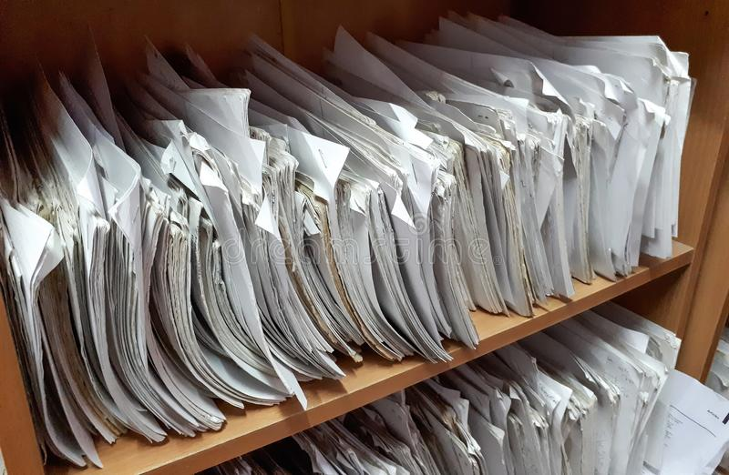 A cupboard full of paper files. / inefficiency of paper based filing system stock photos