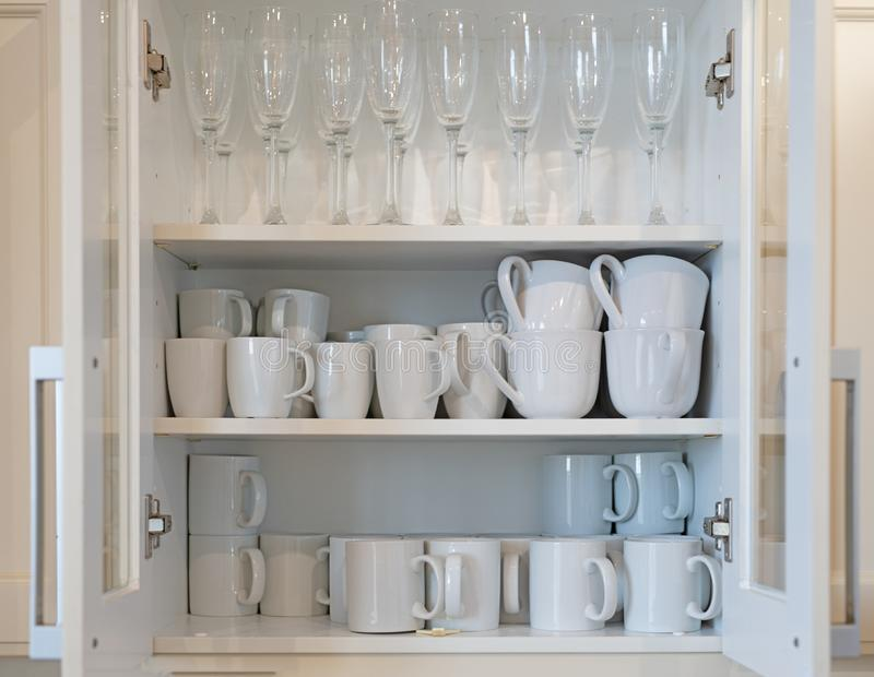 Cupboard full of white mugs stock photos