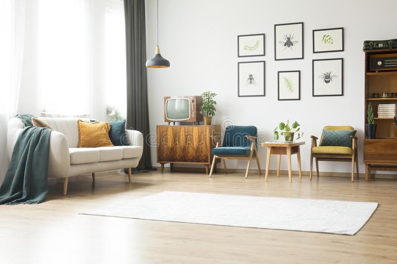 Cupboard with old-fashioned tv. Beige couch, vintage armchairs and wooden cupboard with old-fashioned tv in bright living room interior royalty free stock photo