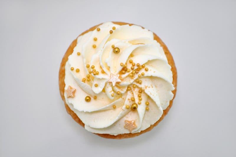 Cupcake με την κρέμα και το χρυσό ψέκασμα βιομηχανιών ζαχαρωδών προϊόντων στοκ φωτογραφία με δικαίωμα ελεύθερης χρήσης