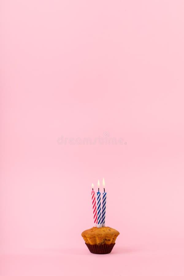 Cupcake avec trois bougies chaudes images libres de droits