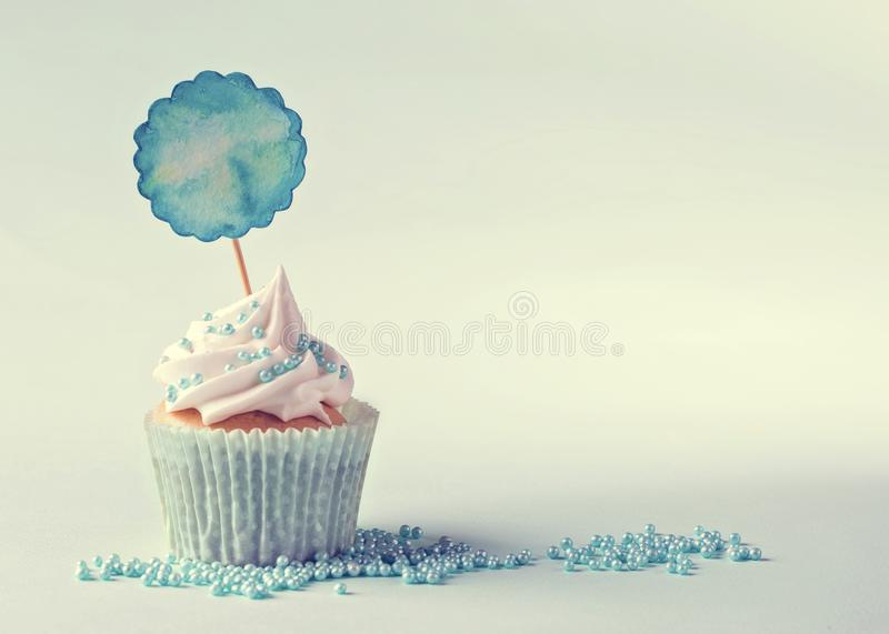 Cupcake with a blue pick. For your text stock images