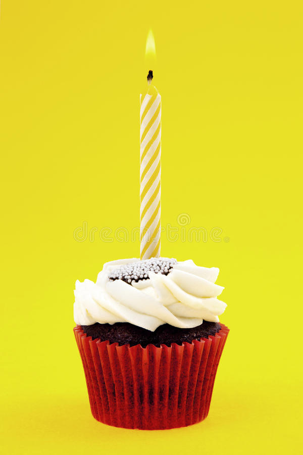Cupcake With Candle. On Yellow Background royalty free stock photography