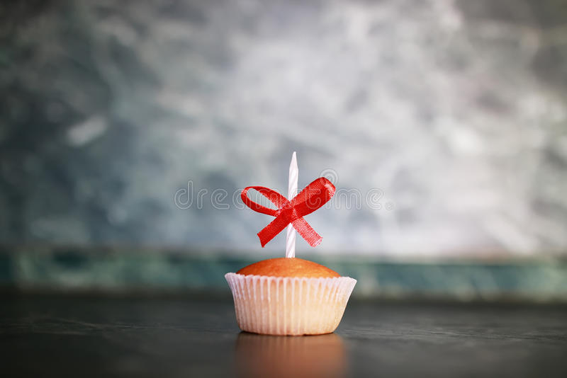Cupcake with a candle holiday. Little delicious cupcake with a candle symbol of celebration events stock photography
