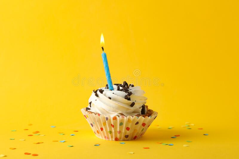 Cupcake with candle on yellow background. Space for text royalty free stock images