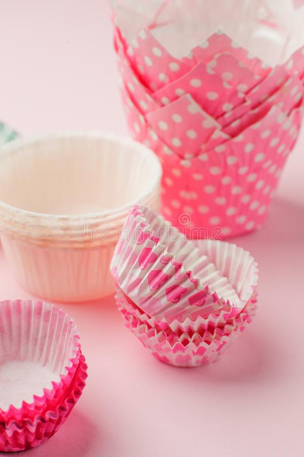 Cupcake cases tower in variety of color and size on pink table ready for holiday celebration, baking concept royalty free stock photography