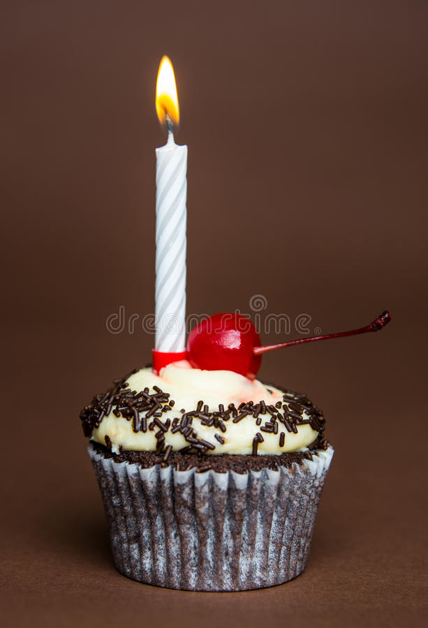 Cupcake. Chocolate cupcake with candle and cherry stock images