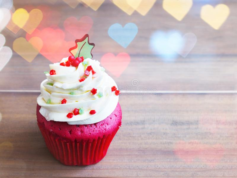 Cupcake with christmas tree shape on wooden table. Close up red velvet cupcake with christmas tree shape on wooden table and heart shape bokeh. Christmas and new stock image