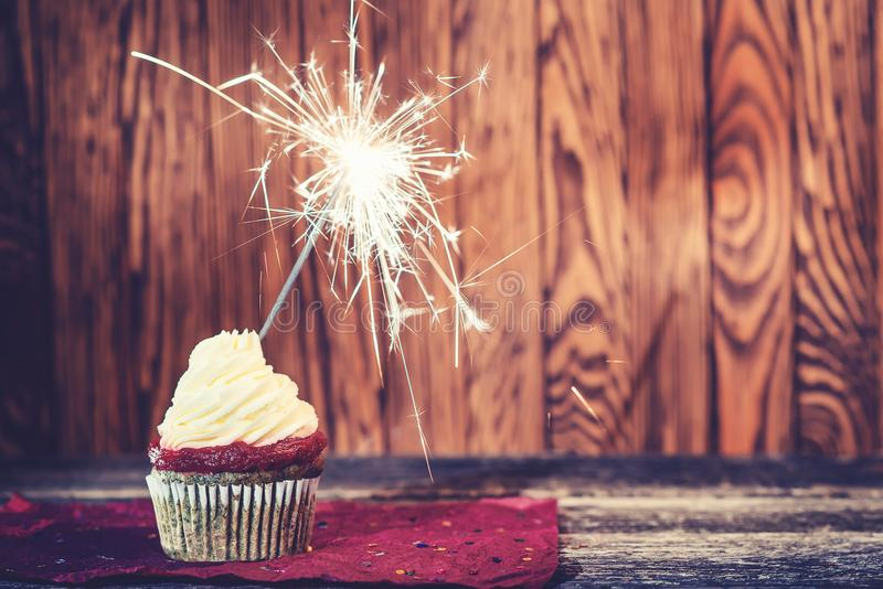 Cupcake with cream cheese, with sparkler on dark wooden background. royalty free stock photography