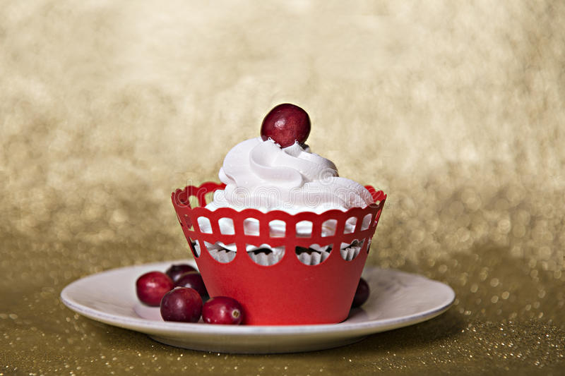 Cupcake with cream and cranberries on Christmas red background stock images