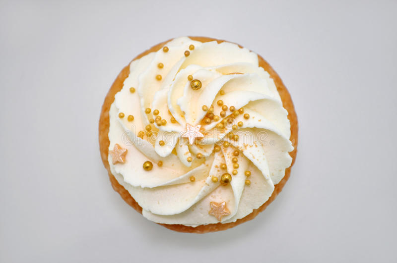 Cupcake with cream and gold confectionery sprinkling. royalty free stock photo