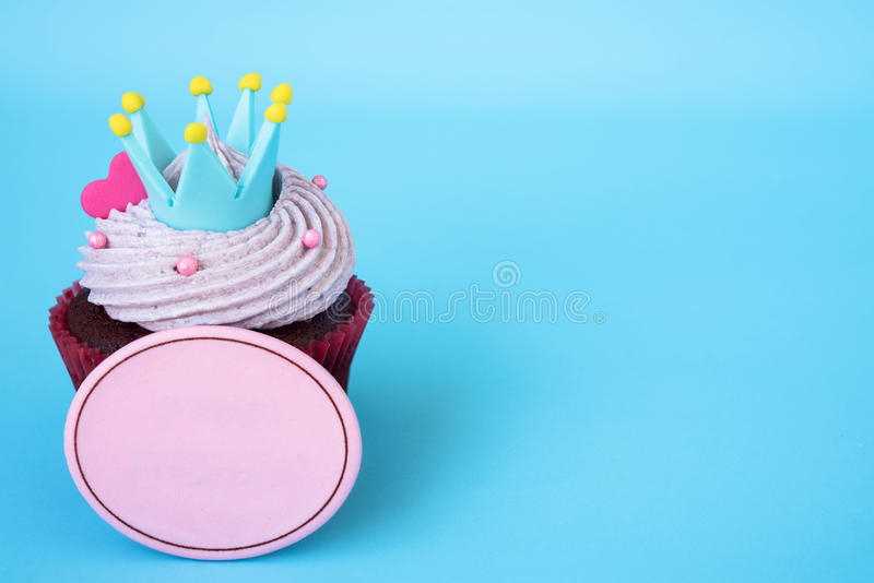 Cupcake with crown and pink heart over blue background. With blank board for text, Gift for celebration stock photos