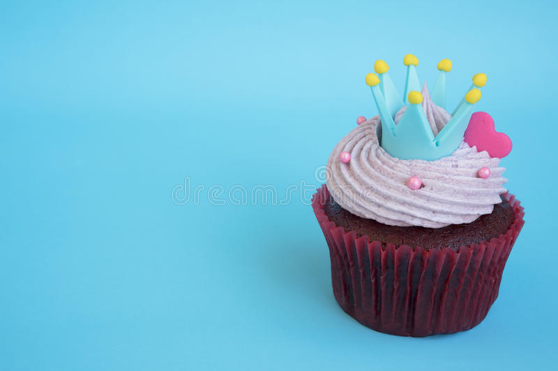 Cupcake with crown and pink heart over blue background. With copy space, Gift for valentine, wedding birthday and anniversary day stock image
