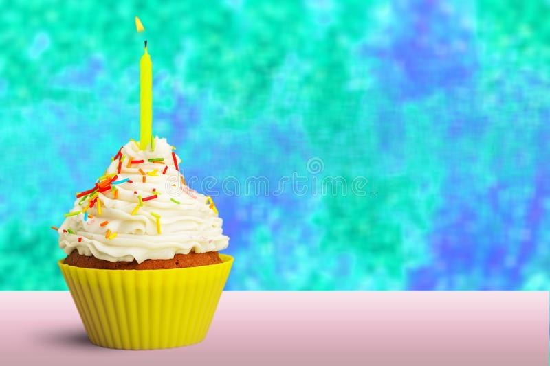 Cupcake decorated with colorful birthday candles royalty free stock images