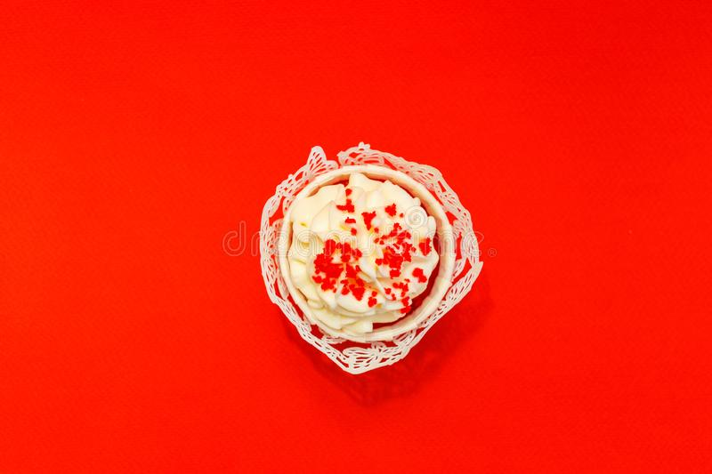 Cupcake with delicate white cream on a red background.  royalty free stock photo