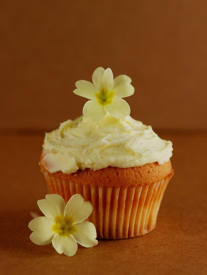 Cupcake die met verse sleutelbloembloemen wordt verfraaid royalty-vrije stock afbeeldingen