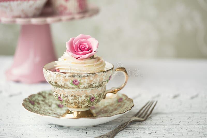 Cupcake in een uitstekend theekopje royalty-vrije stock afbeeldingen