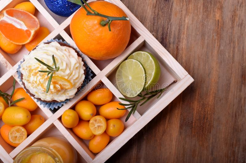 Cupcake garnished with butter cream, citrus curd, kumquats, mandarins, lime and Christmas balls in a wooden box royalty free stock photography