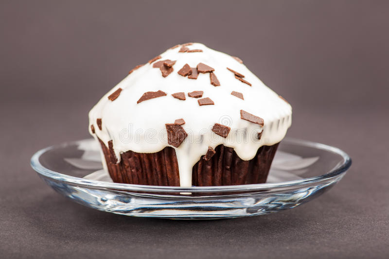 Cupcake in a glass saucer. On a dark background stock photo