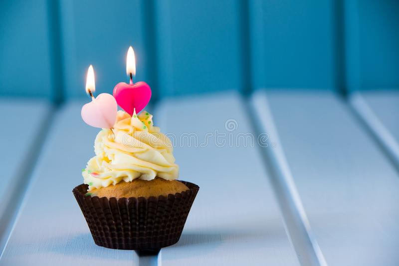 Cupcake with a heart shaped candles for 2 - second birthday. Birthday's cake - cupcake with a heart shaped candles for 2 - second birthday or valentine's day royalty free stock images
