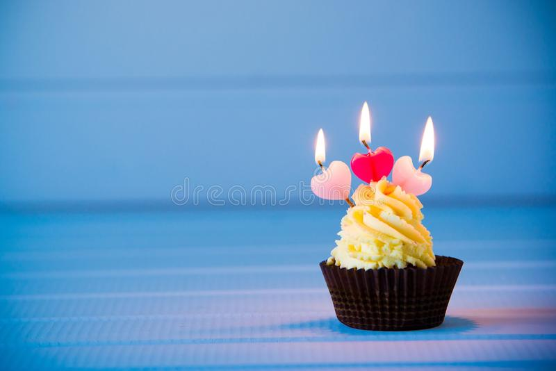 Cupcake with a heart shaped candles for 3 - third birthday royalty free stock photo